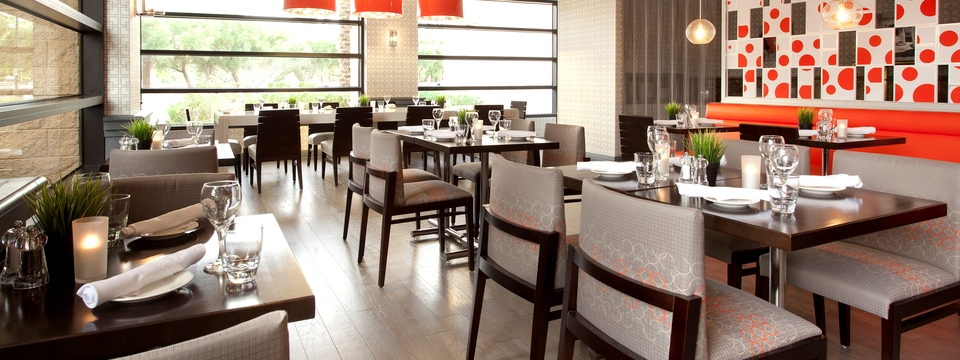 Well-lit hotel restaurant with square tables and gray chairs