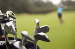 Close up of a golf bag with golfer on the green in background