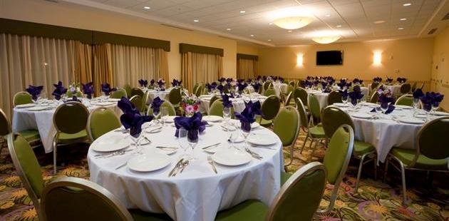 Banquet space with green chairs and round tables