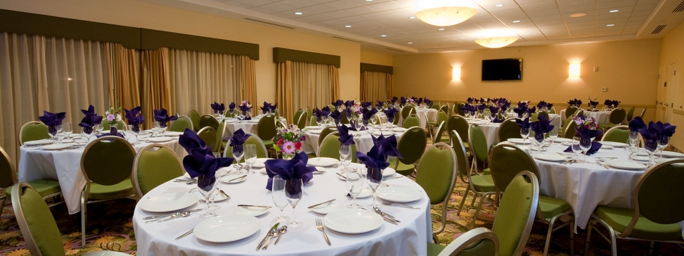 Banquet space with round tables, green chairs and purple napkins