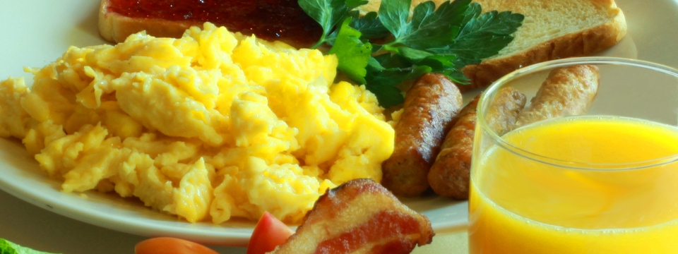 Breakfast plate with scrambled eggs, toast and sausage