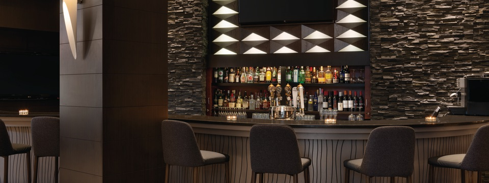 On-site lounge with high-top chairs and a fully stocked bar