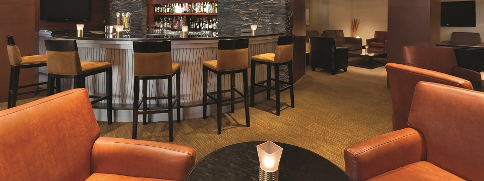 Lounge with view of bar stools and curved bar counter