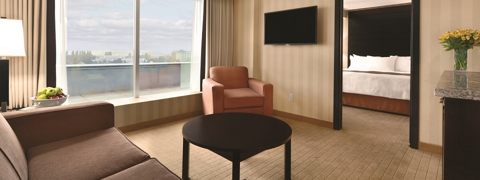 Suite's living area with sofa, coffee table and wall-mounted TV