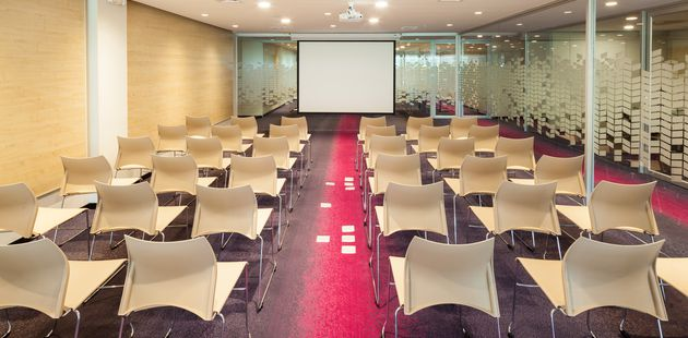 Meeting room with glass walls and chairs facing a projector screen