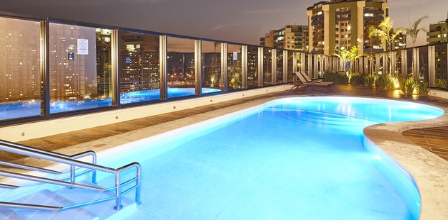 Outdoor rooftop pool lit up at night