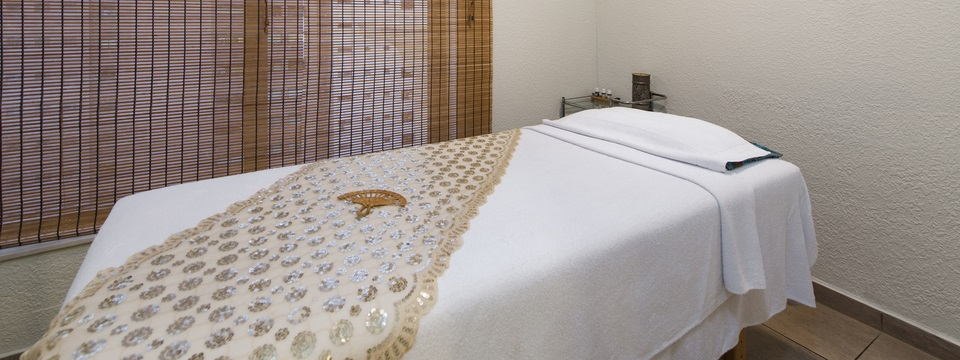 Massage table with white linens and a wooden fan on top