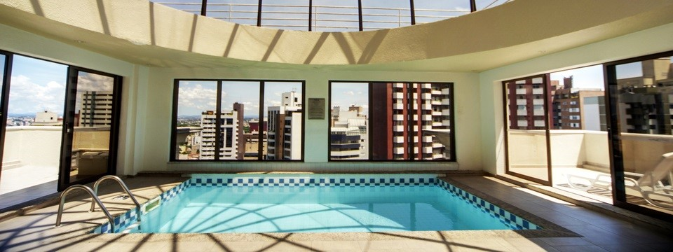 Enclosed rooftop pool with views of Curitiba