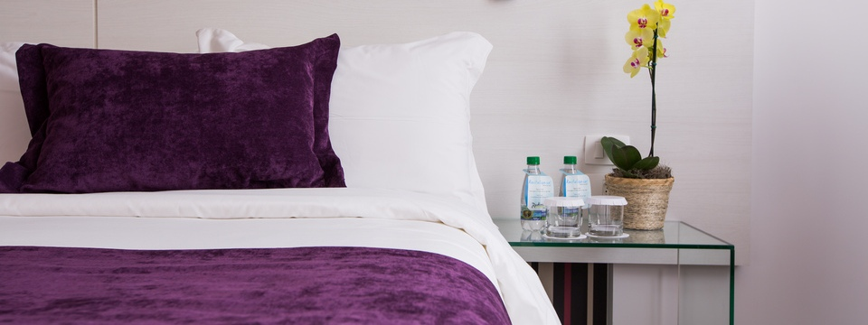 Bed with white sheets and velvety purple pillow