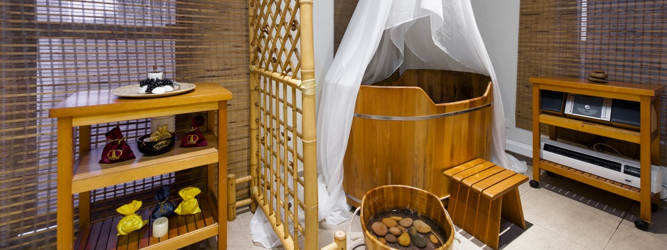 Wooden tub enveloped by a sheer white curtain in our hotel spa