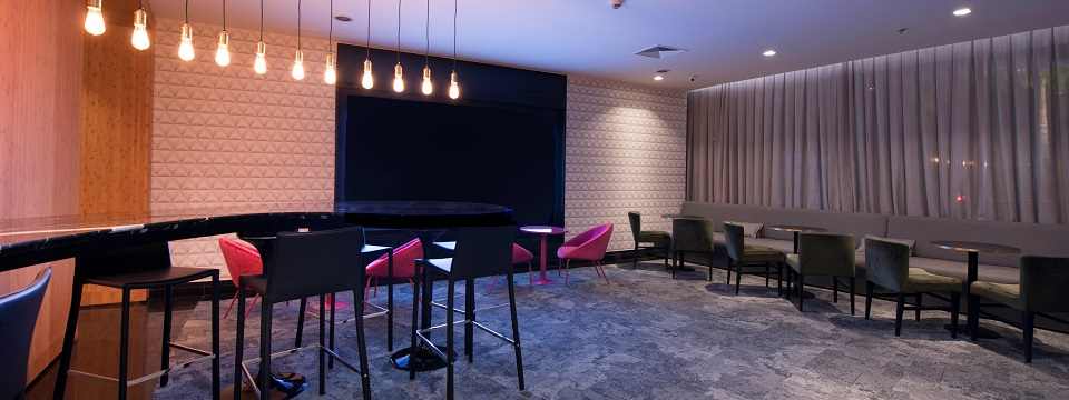 Lobby Bar with neon pink chairs and dark gray booths