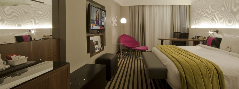 Mod hotel room with neon pink chair and work desk