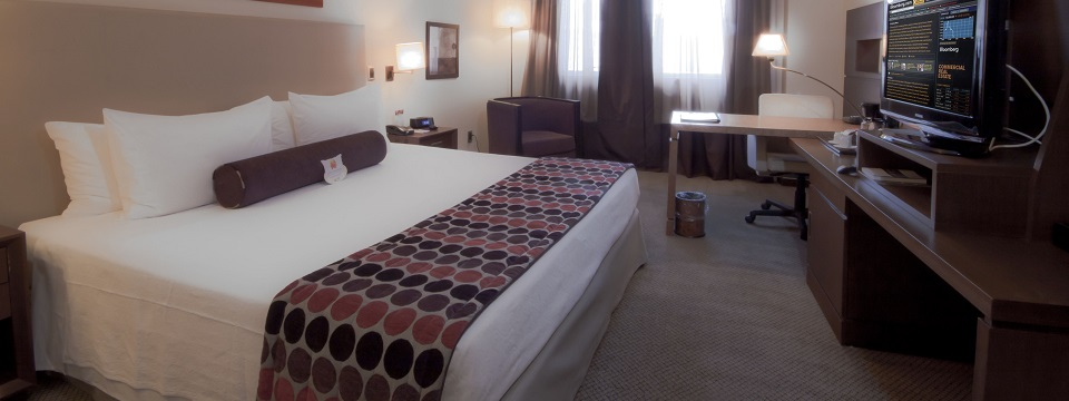 Hotel room with king bed, desk and flat-screen TV