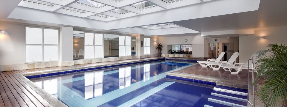 Well-lit indoor pool with lounge chairs at Barueri hotel