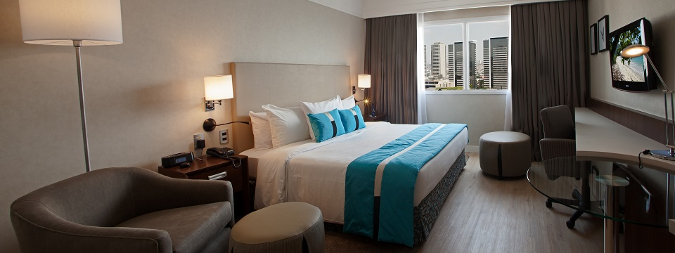 Bright blue accents in hotel room with city view