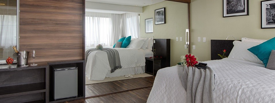 Suite's queen bed and minibar with fridge