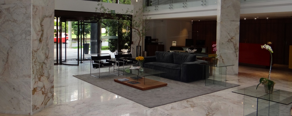 Modern lobby with marble detailing, a comfortable couch and greenery