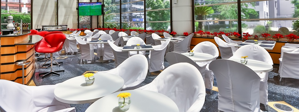 White tables and chairs, bar and flat-screen TV in lounge