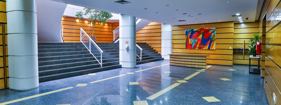 Hotel lobby with staircase, tree and modern artwork