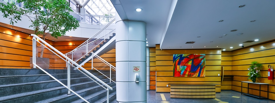 Modern staircase leading past tree in lobby