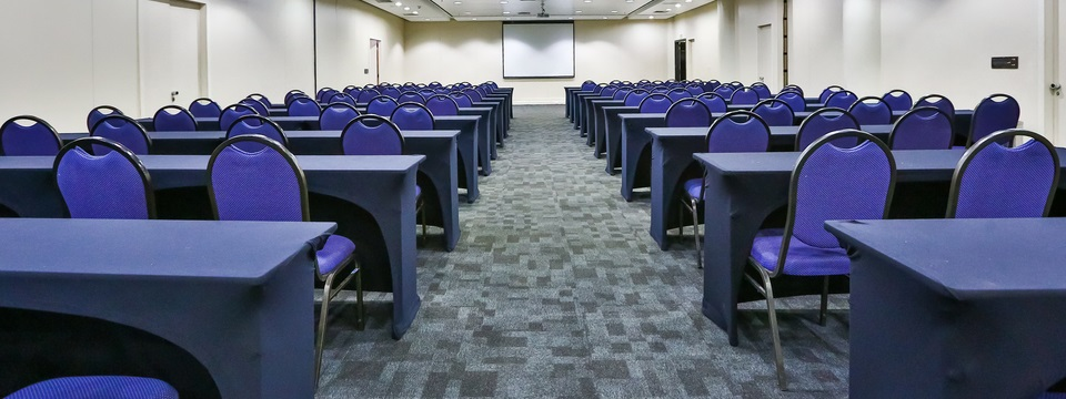 Meeting room with rows of tables and purple chairs