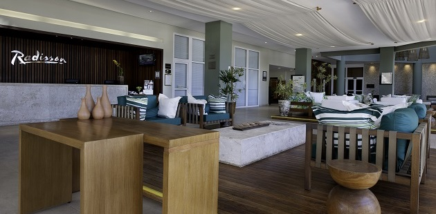 Hotel lobby with couches and chairs that have teal accents