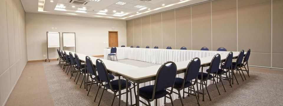 Tables aligned in U-shape surrounded by chairs in meeting room