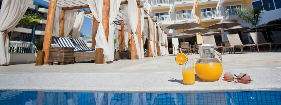 Pitcher of orange juice and a pair of sunglasses on the side of the pool
