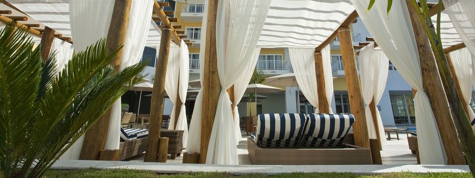 Striped lounge chairs beneath shade curtains at the outdoor pool