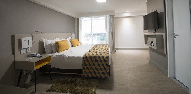 Spacious room with king bed, bedside table and wall-mounted TV