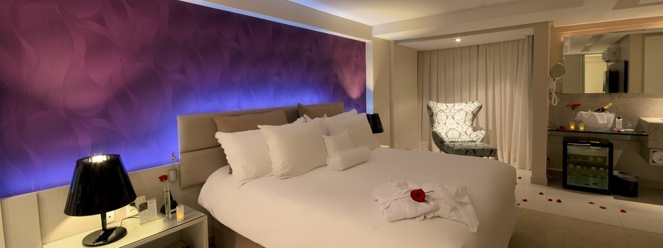 Room with king bed, bedside tables and a minibar