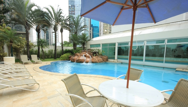 Outdoor pool with chairs and water feature