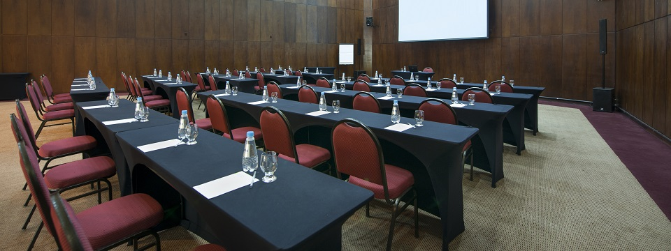 Meeting room with rows of tables and chairs