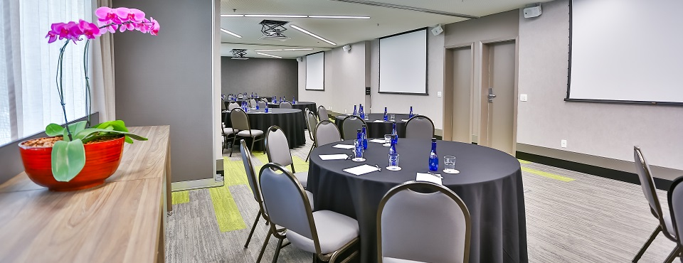 Event space with round tables, bottled waters, and multiple projector screens