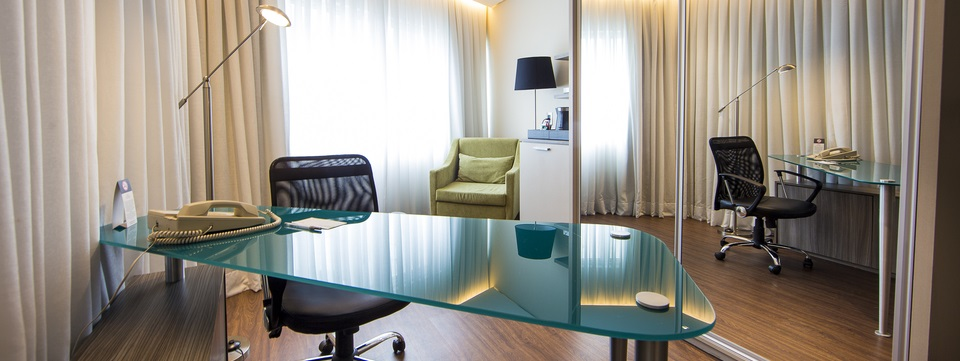 Modern work space with table and ergonomic chair in suite