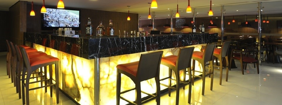 Alcoholic beverages sitting on marble bar top at hotel