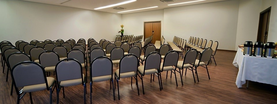 Rows of chairs in meeting space with blank white walls