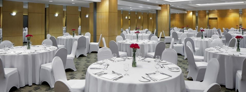 Bruneian meeting space featuring round tables with white linens