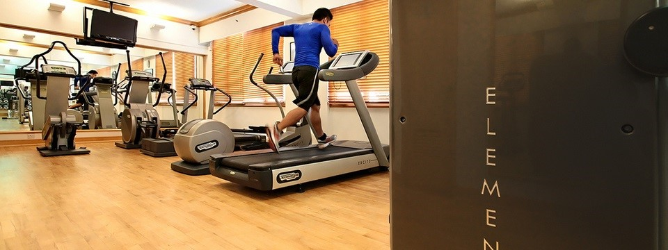 Man runs on treadmill in hotel's fitness centre with a flat-screen TV
