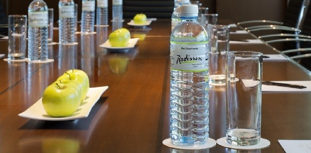 Bruneian meeting space with complimentary water and green apples