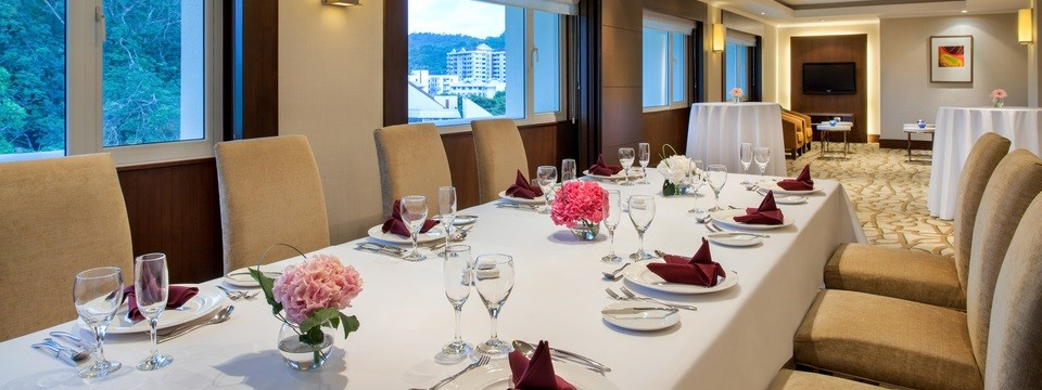 Private dining setup featuring a white tablecloth, pink floral centerpieces and burgundy napkins