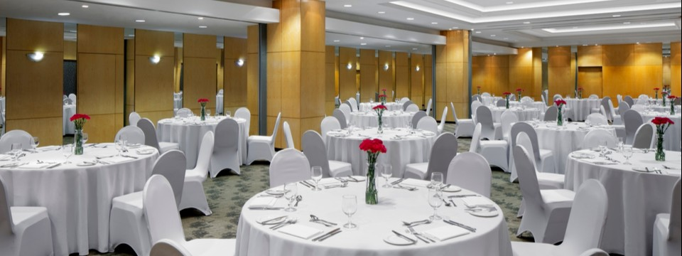 Ballroom featuring round tables with white linens and red flower centerpieces