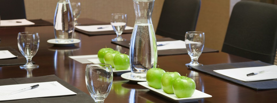 Meeting room table with water and apples