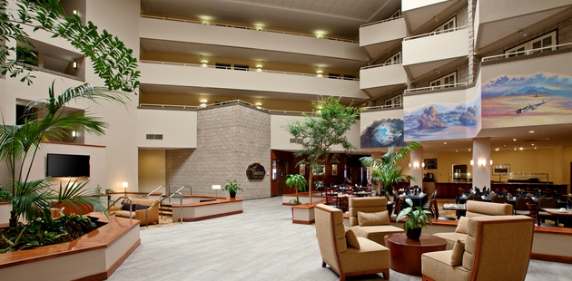 Spacious lobby with tables, chairs and greenery