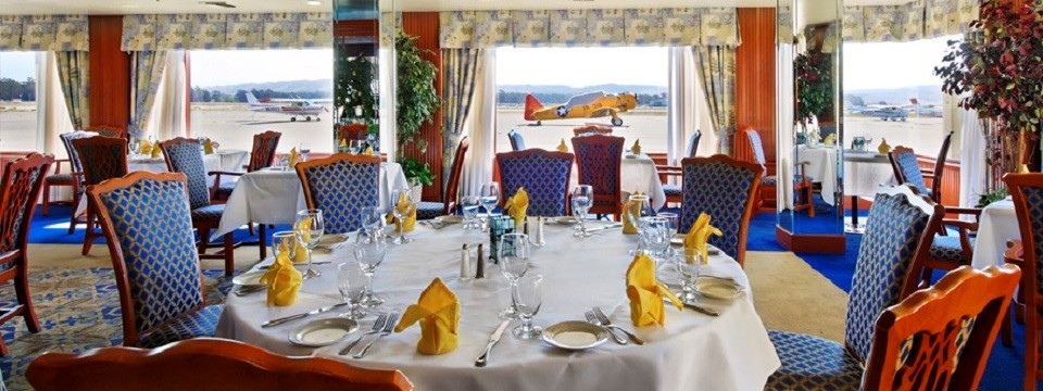 Colorful restaurant dining room with blue patterned chairs and yellow napkins