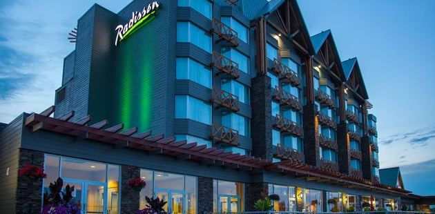 Edmonton hotel exterior with green lights and balconies