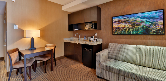 Hotel suite with dining table, wet bar and sleeper sofa