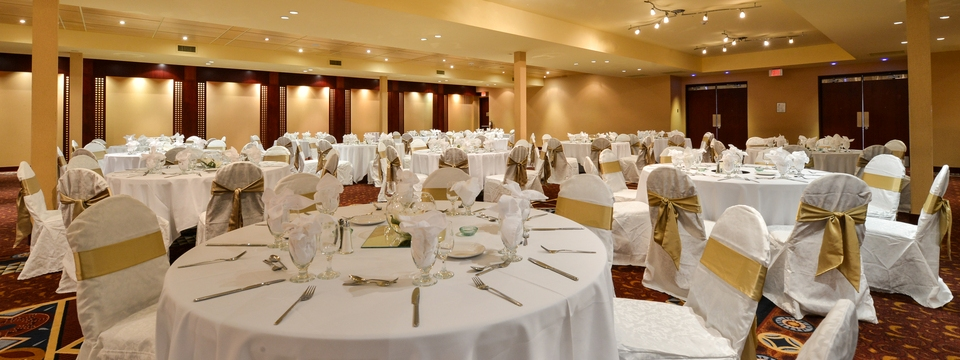 Ballroom tables with white tablecloths and gold accents