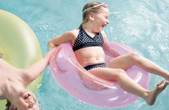 Two children playing on floats in a swimming pool