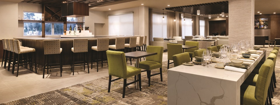 On-site restaurant with tables, green chairs and a bar area